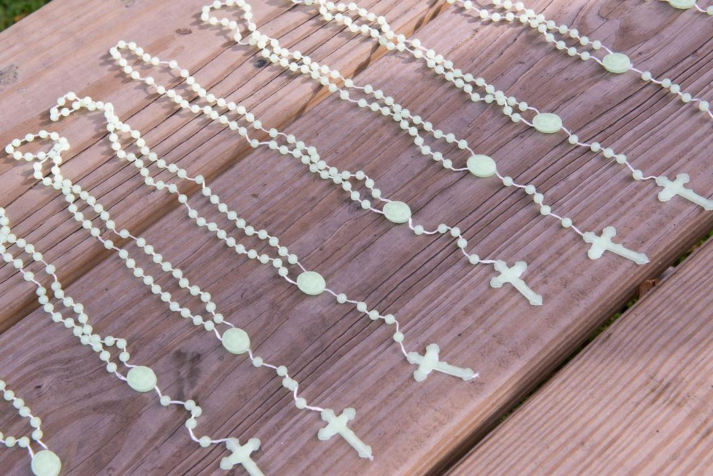 Rosaries are arranged on a table.