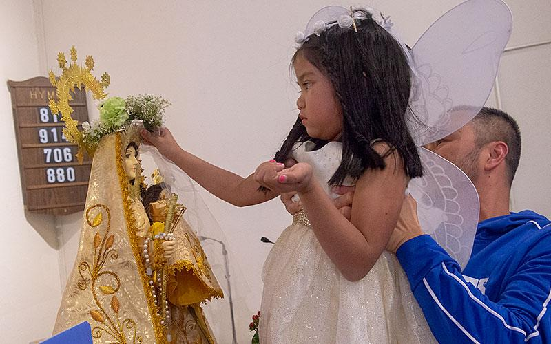 Angelica Blancaflor places a crown of flowers upon the head of a statue of the Blessed Virgin Mary.