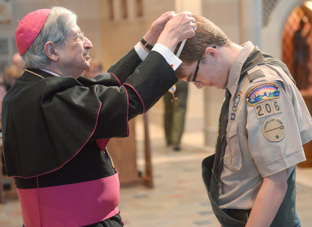 Bishop Salvatore R. Matano places the Ad Altare Dei emblem around the neck of Daniel Rook during the 2019 Catholic Scouting Religious Emblem Service at Sacred Heart Cathedral Feb. 2. (Courier photo by John Haeger)
