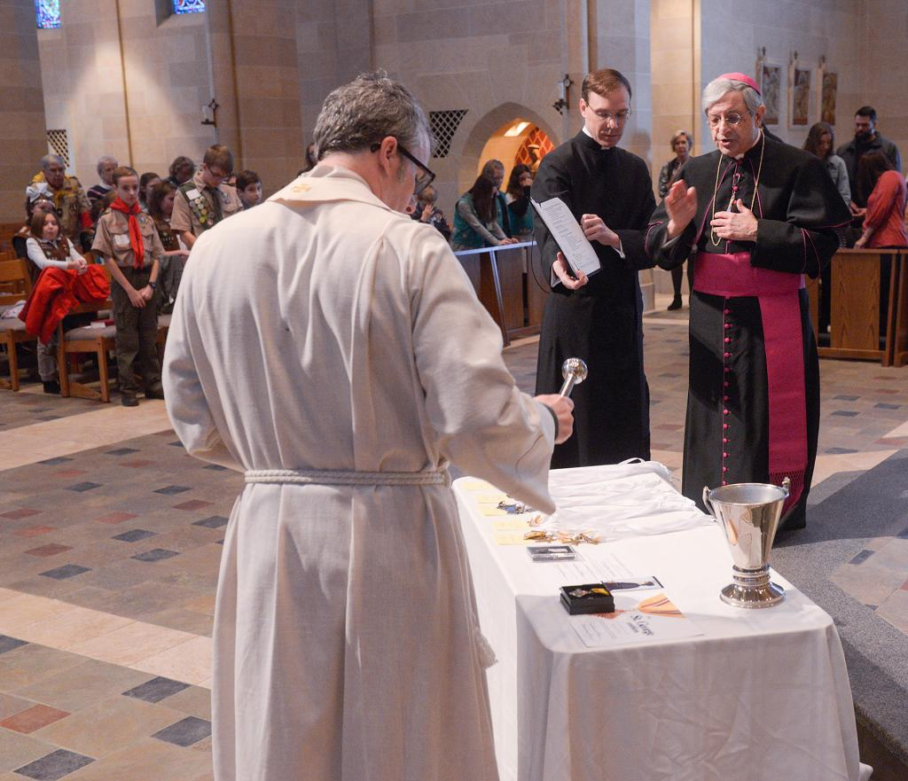 Bishop Matano and Father McGrath bless the emblems. (Courier photo by John Haeger)