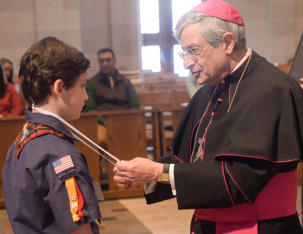 Bishop Matano places the Light of Christ emblem around the neck of Aiden Colvin. (Courier photo by John Haeger)