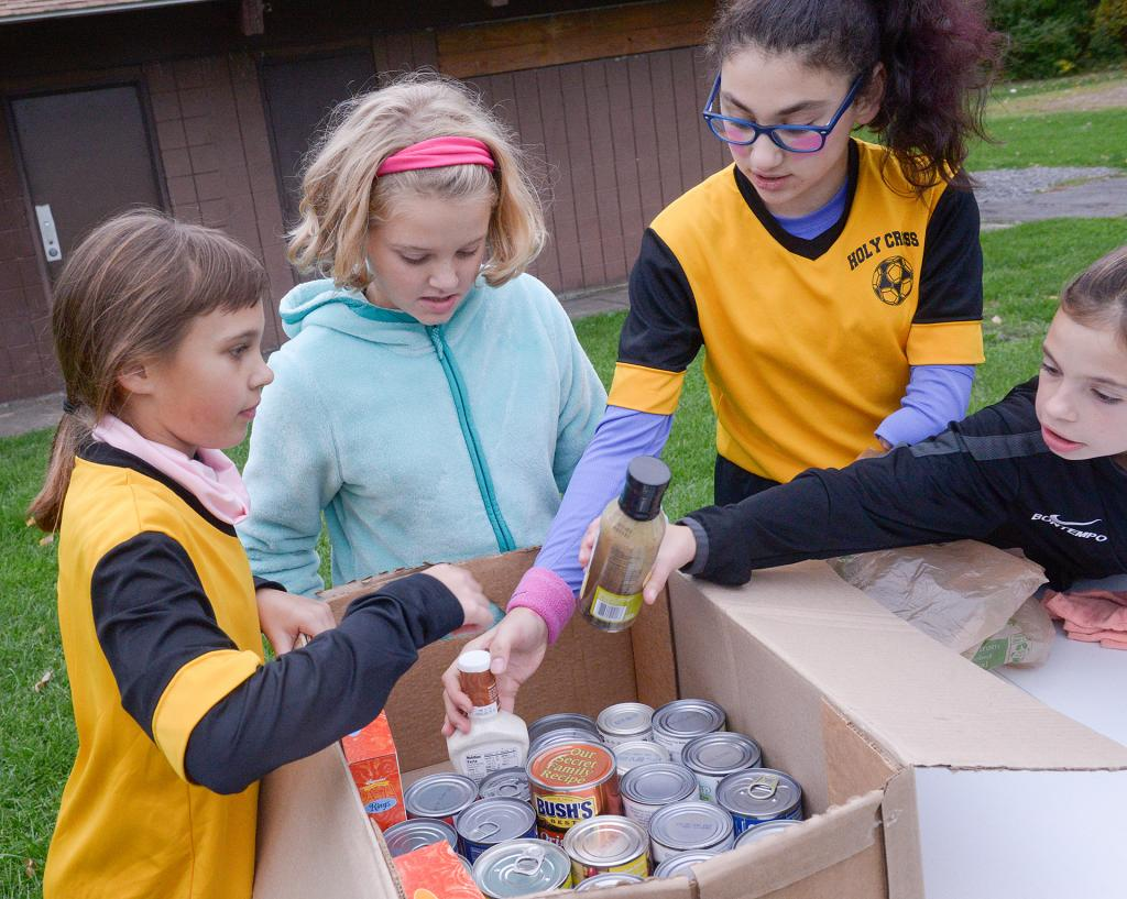 Ella Kehoe, Luis Santangelo, Brooklyn Tortorice and Lillian Bontempo from Holy Cross Church box up food items collected during the Friday Night Under the Lights CYO soccer event at Basil Marella Park in Greece Oct. 12. (Courier Photo by John Haeger)