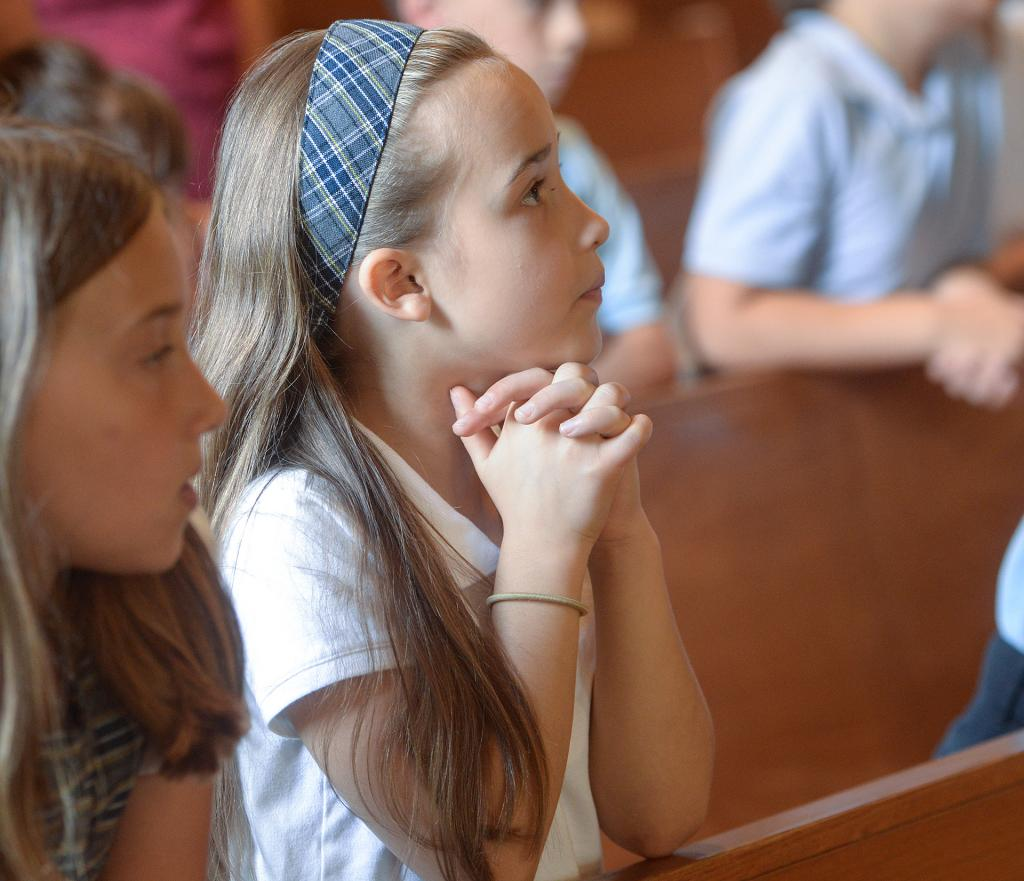 Linden Gawronski prays during the back-to-school Mass for St. Joseph School in Penfield Sept. 7. (Courier Photo by John Haeger)