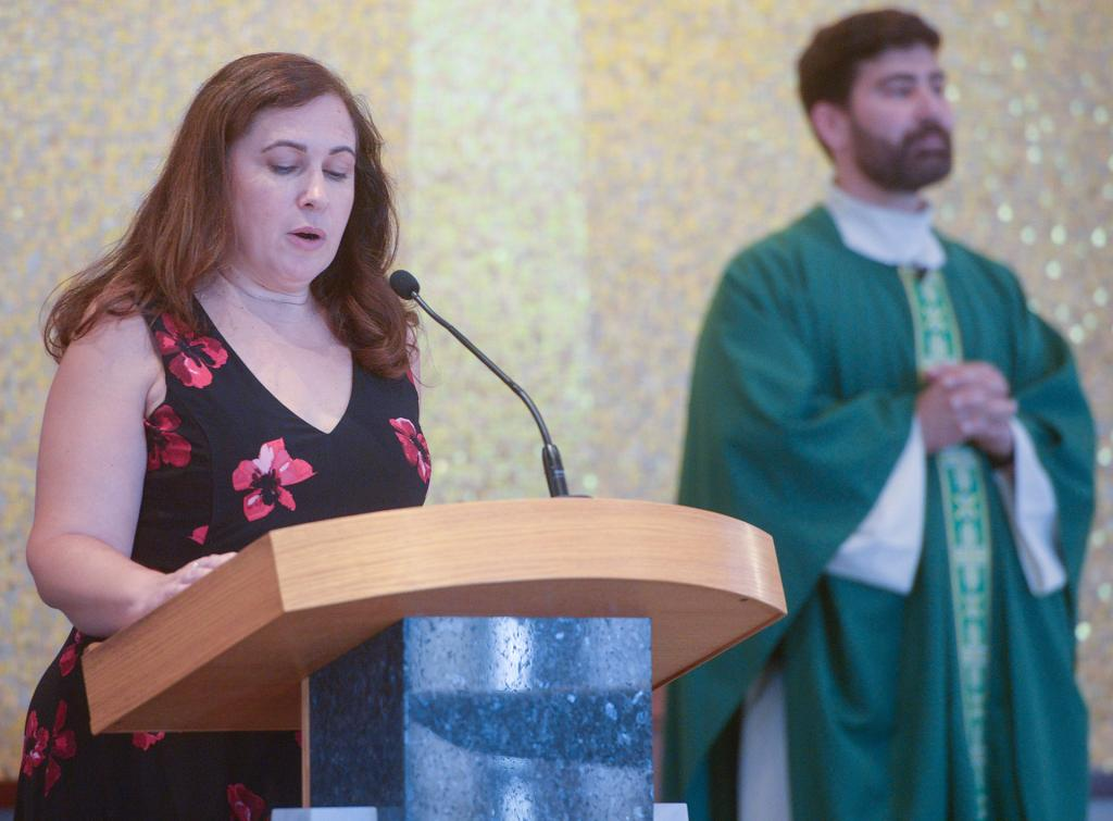 St. Joseph School Principal Amy Johnson takes part in the Mass. In the background is Father Jeffrey (Courier Photo by John Haeger)