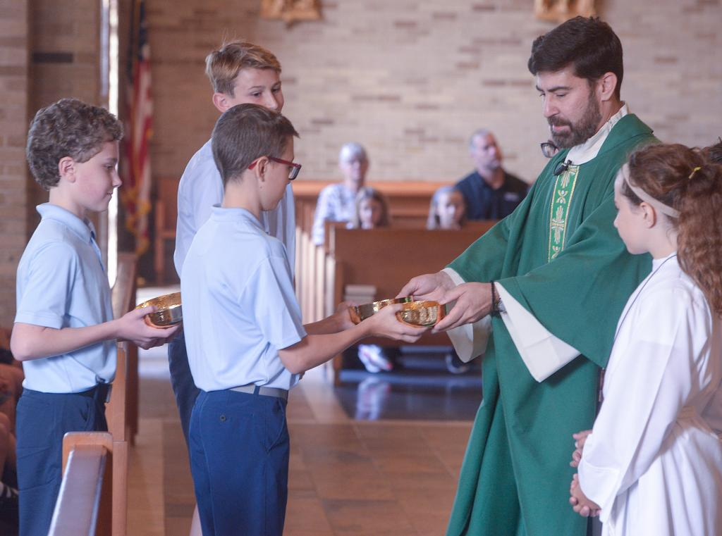 Father Jeffrey Chichester receives the gifts from St. Joseph students Thomas O'Neill, Jack Callery and Matthew Kozara. (Courier Photo by John Haeger)
