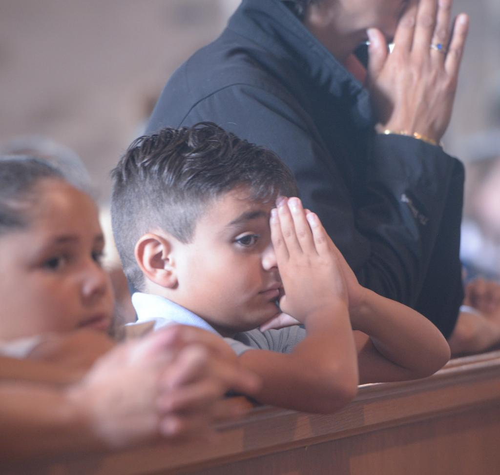 Spencer Yarid prays during the Mass. (Courier Photo by John Haeger)