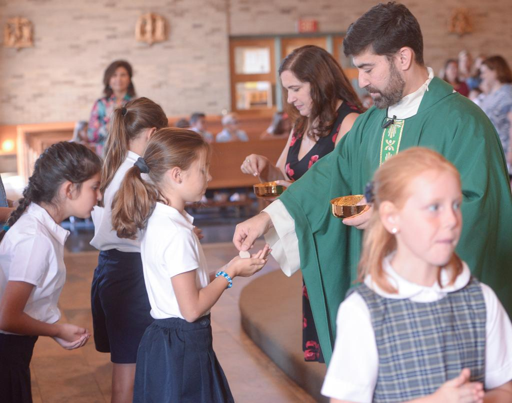 Brynn Henry receives Communion from Father Jeffrey Chichester. (Courier Photo by John Haeger)