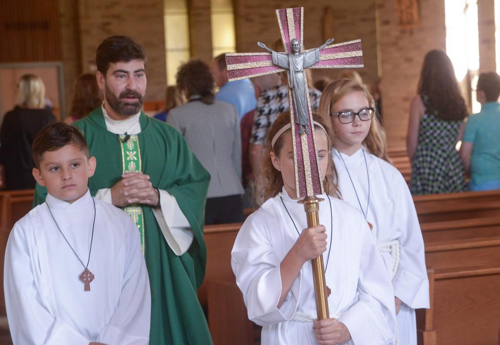 Father Jeffrey Chichester and altar servers Brody Yarid, Alexandra Edwards and Ireland Carangelo recess from Mass. (Courier Photo by John Haeger)