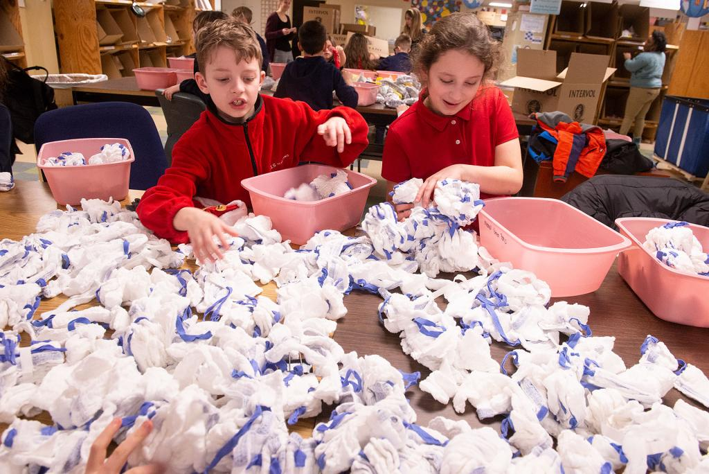 St Lawrence School third-graders Michael Francis and Adrianna DiLettera sort items at InterVol in Rochester Jan. 30 as part of their service project for Catholic Schools Week. (Courier photo by John Haeger)