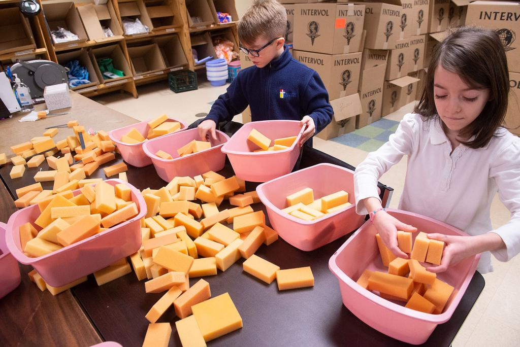 St Lawrence School third-graders George Martone and Hailey Francis sort items at InterVol. (Courier photo by John Haeger)