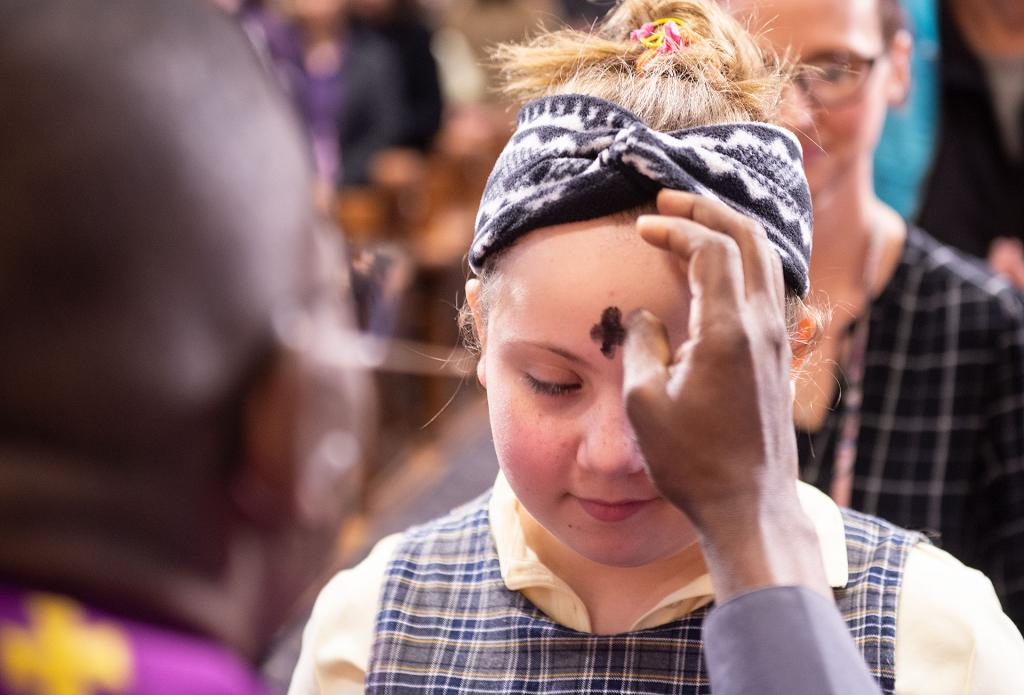 Father Clifford Dorkenoo imposes ashes on the forehead of Leiliah Garrett, a fifth-grader at St. Mary School in Canandaigua.