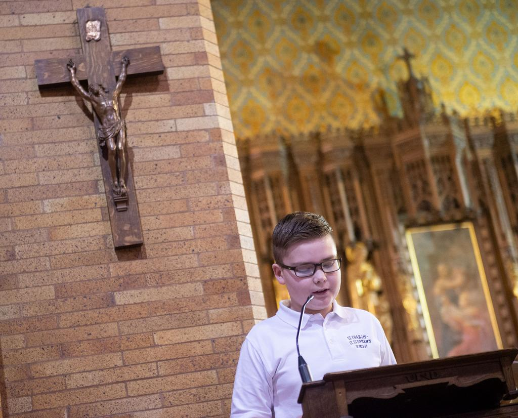 Jamie Ninestine, a student at St. Francis-St. Stephen School in Geneva, proclaims the first reading during an Ash Wednesday liturgy at St. Stephen Church Feb. 26.