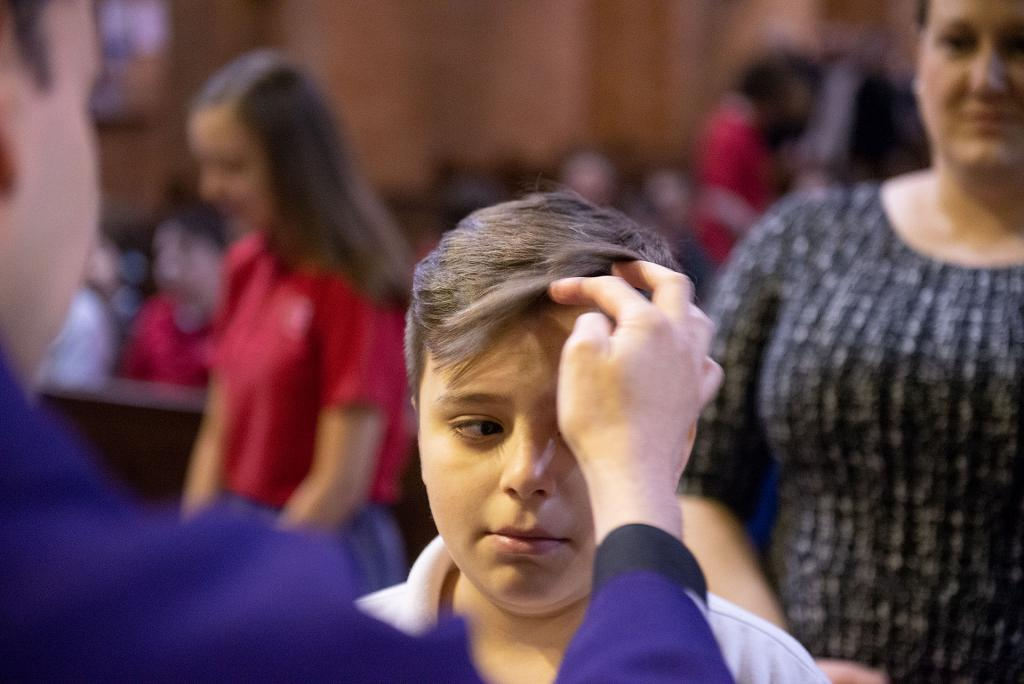 Max Delgado, a student at St. Francis-St. Stephen School, receives ashes from Father Sanchez.