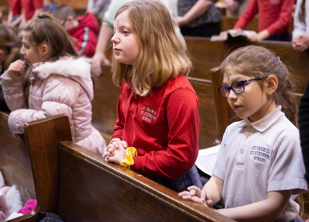 Molly Lamson and Alena Austin, students at St. Francis-St. Stephen School, pray during the liturgy.