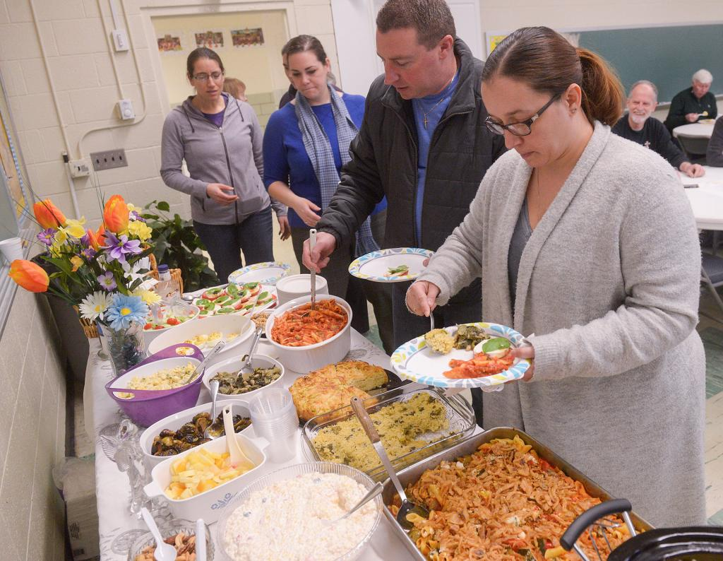 Jami Ross places food on her plate during the celebration.<br /> (Courier photo by John Haeger)