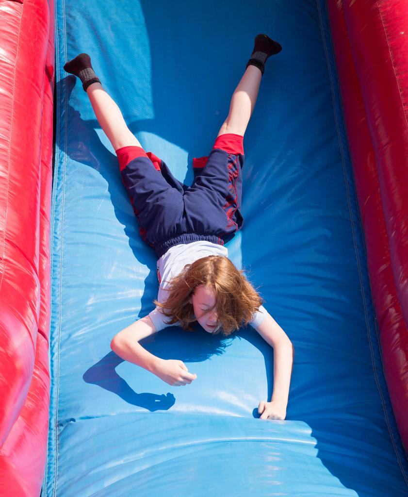 Bright Robak, 11, goes down the slide head first during the annual Field Days at St. Michael School in Penn Yan June 18.