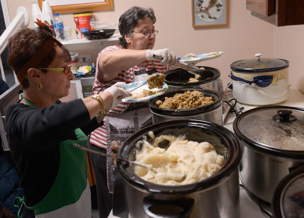Diamond Auble and Kathy DiMaria, members of St. Frances Xavier Cabrini Parish's peace and social-justice committee, prepare plates during a Thanksgiving dinner at the Father Tracy Health & Wellness Center Nov. 14.(Courier Photo by John Haeger)