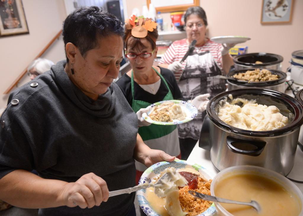 Miriam Cortes, Diamond Auble and Kathy DiMaria, members of St. Frances Xavier Cabrini Parish's peace and social-justice committee, prepare plates Nov. 14 during the Thanksgiving dinner at the Father Tracy Health & Wellness Center.(Courier Photo by John Haeger)