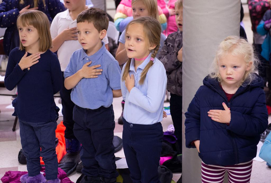 Students from St. Michael School in Penn Yan stand for the national anthem during a Veterans Day ceremony at St. Michael Church Nov. 12.