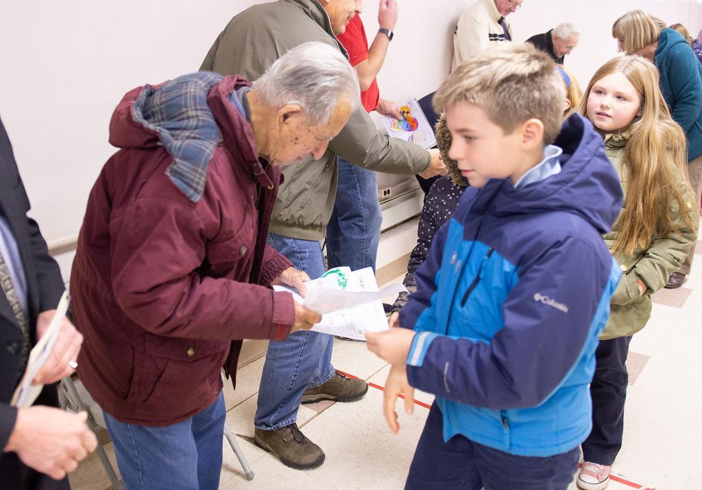 St. Michael School third-grader William Boutard-Hunt gives a card he made to a World War II veteran.