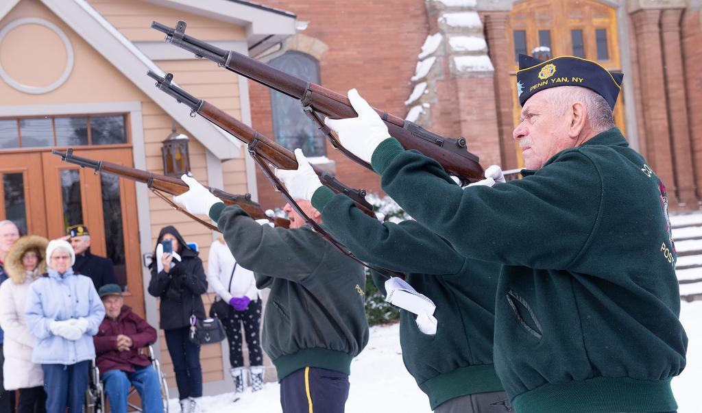 """Honor guard members fire a salute before """"Taps"""" is played."""