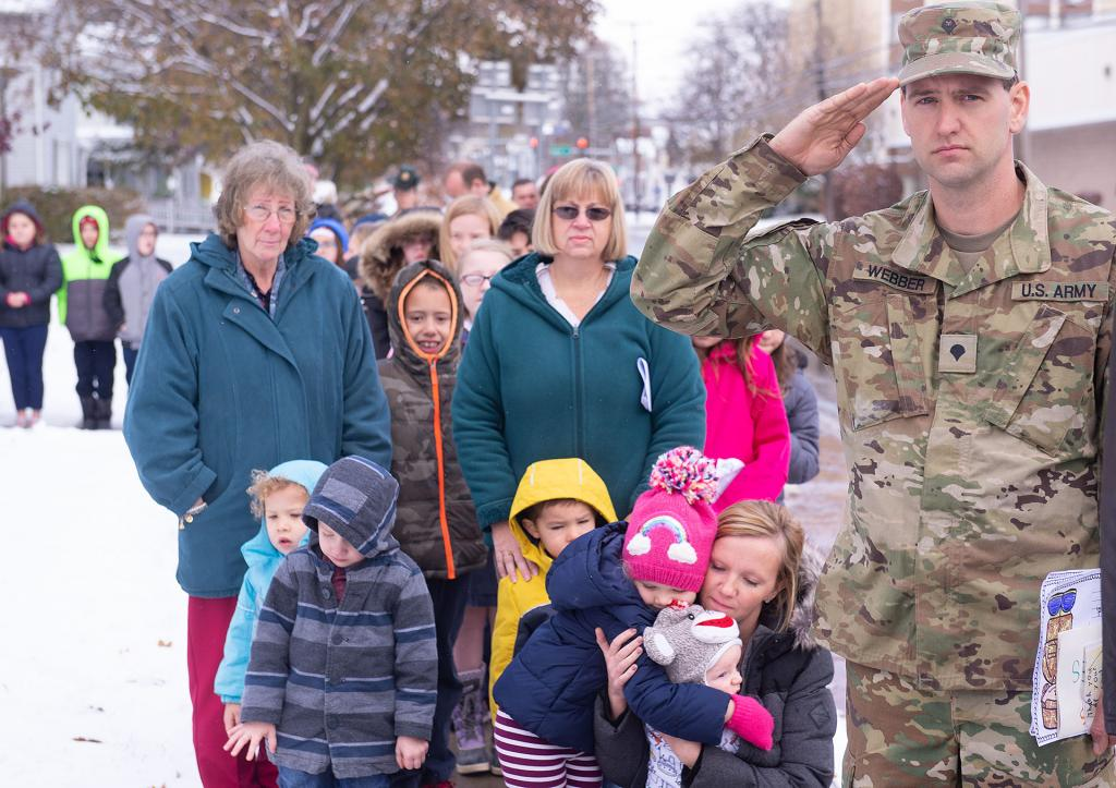 """U.S. National Guard Specialist Paul Webber salutes as students and staff from St. Michael School look on as """"Taps"""" is played."""