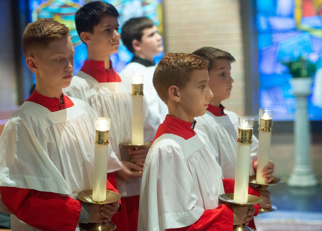 Altar servers look on during the Mass.