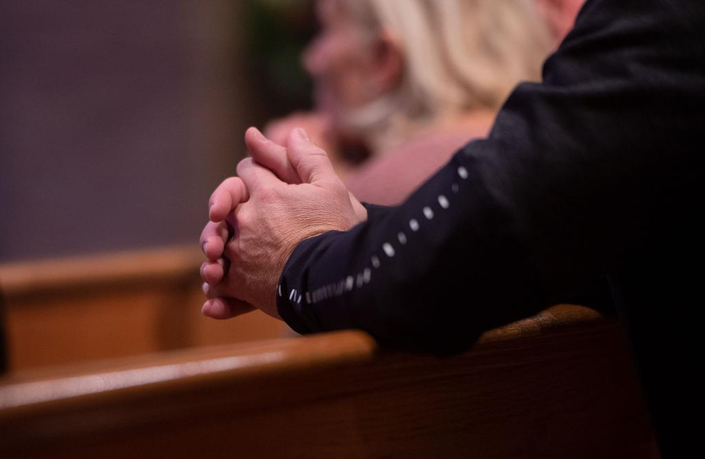 A congregant prays during the Mass.