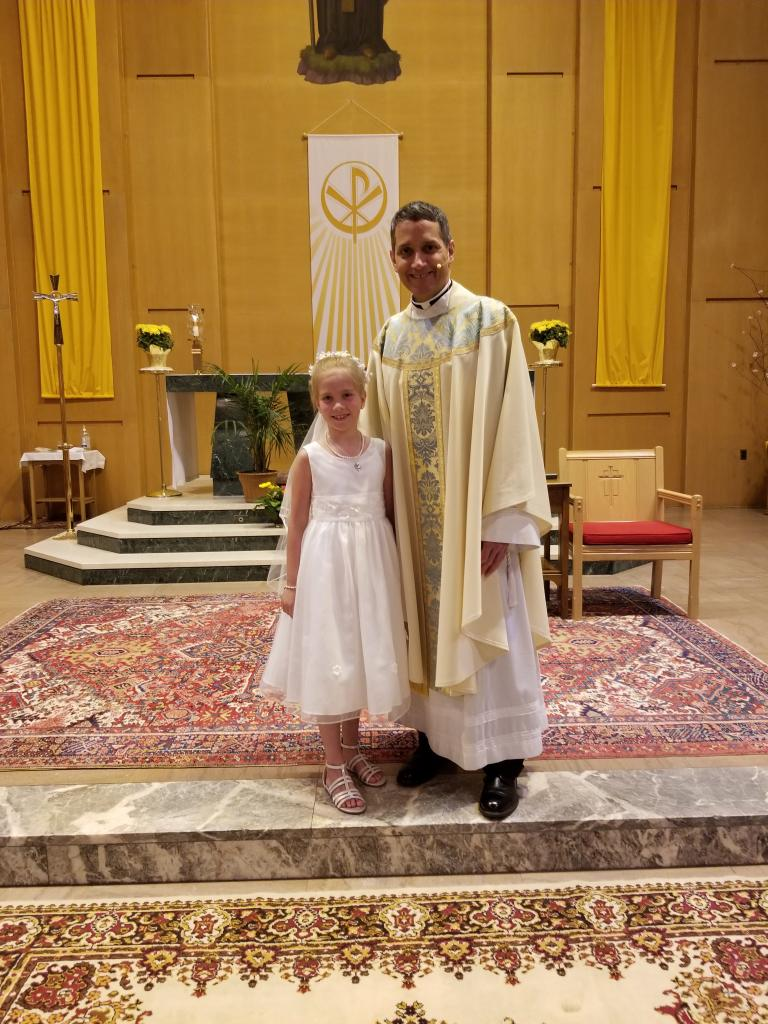 Molly (left) with Father John Loncle, pastor of Southeast Rochester Catholic Community (St. Boniface, St. Mary and Blessed Sacrament). Molly received her First Holy Communion at St. Boniface Church. (Submitted by mom, Erin)