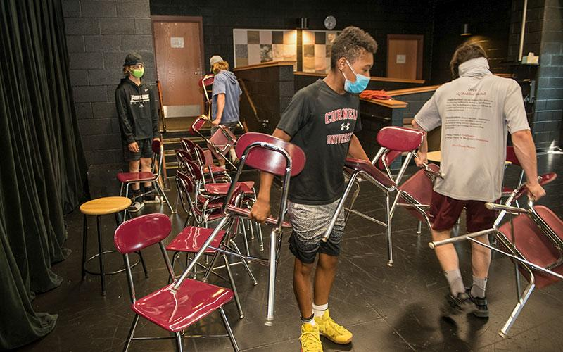Tre' Walker (from left) and Lucas Leone move excess seats to storage at Aquinas Institute of Rochester in preparation of the school's reopening Aug. 24th.