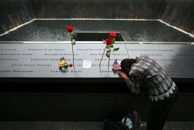 A woman grieves at the inscription of her late husband's name at the edge of the North Pool near the national 9/11 Memorial in New York City Sept. 11.