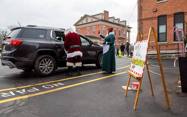 <p>Santa and Mrs. Claus speak to children through a car window during a drive-through visit with Santa Claus Dec. 5 at Canandaigua&rsquo;s St. Mary School. (Courier photo by Jeff Witherow)  </p>
