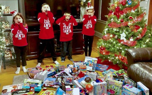 <p>Gia Masters (from right) poses with the toys she was able to purchase with donated funds. With her is her brother, Mikey, and her cousins CJ and Sami Urban. (Photo courtesy of Luz Segnini)  </p>