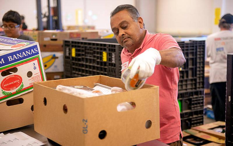 <p>In 2017, volunteer Pankaj Patel boxes up meats at the Food Bank of the Southern Tier to be shipped to food pantries. (Courier file photo)  </p>