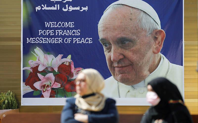 <p>Women stand near a poster of Pope Francis in Baghdad March 3, 2021. Pope Francis plans to visit Iraq March 5-8. (CNS photo by Khalid al-Mousily/Reuters)  </p>