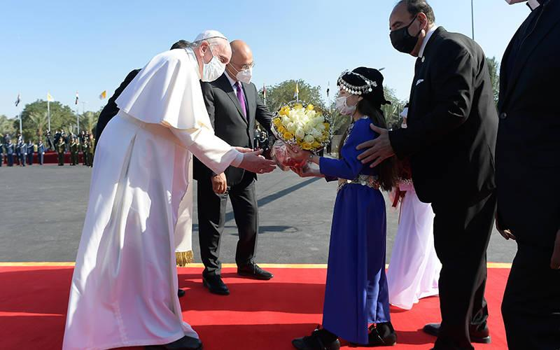 <p>Pope Francis receives flowers from children during a welcoming ceremony with Iraqi President Barham Salih at the presidential palace in Baghdad March 5, 2021. (CNS photo by Vatican Media)  </p>