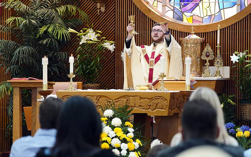 <p>Father John Crozier elevates the Eucharist during Easter Mass April 4, 2021, at St. Peter the Apostle Church in Islip Terrace, N.Y., amid the coronavirus pandemic. (CNS photo by Gregory A. Shemitz)  </p>