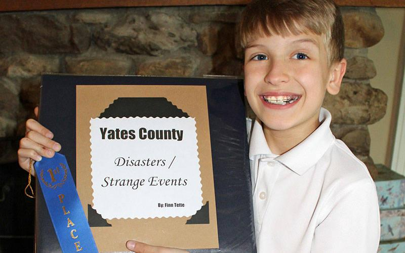 <p>Finn Tette, a fourth-grader at St. Michael School in Penn Yan, won first prize in the school&rsquo;s Local History Fair for his research project on disasters and strange events in Yates County. (Photo courtesy of Kristin Burch)  </p>
