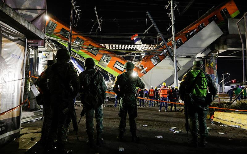 <p> Soldiers stand as rescuers work at a site where an overpass for a metro partially collapsed May 3, 2021, with train cars on it at Olivos station in Mexico City. Picture taken May 4, 2021.</p>