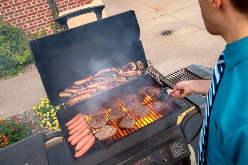 <p>Burgers and hot dogs are prepared during a Grilling with God event at St. John the Evangelist Church in Rochester in 2018. (Courier file photo)  </p>