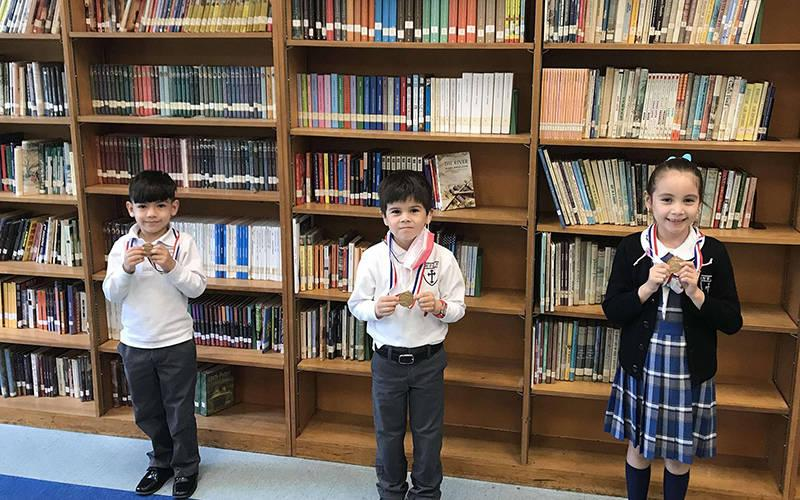 <p>Holy Family Catholic Academy students from New York City show their handwriting medals for winning the state competition. From left are first graders Arron Morocho Kgn and Jake Mulryan, 2021 winners, and 2020 first-grade winner Isabella Ordonez. (CNS photo courtesy Diocese of Brooklyn)  </p>