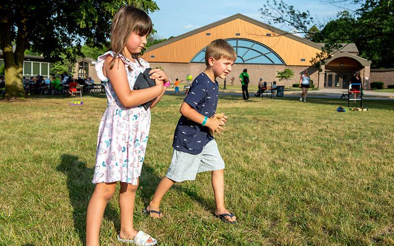 <p>Kara and Michael Bellavia play a bag-toss game at St. Rita Church in Webster during a June 26 Food Truck Rodeo. (Courier photo by Jeff Witherow)  </p>