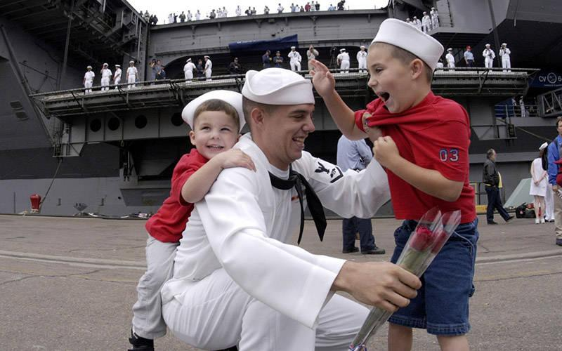 <p>A sailor aboard the USS Constellation in San Diego is greeted by his children in this 2003 file photo. The invitation to move outside of the self to the other is the divine pedagogy of fatherhood. (CNS photo by Jaime Recto/Reuters)  </p>