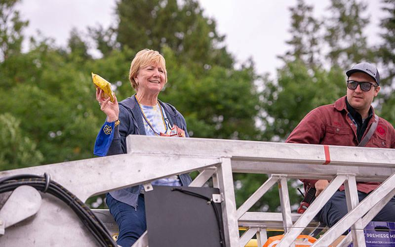 <p>Mary Ellen Wagner, principal of St. Rita School in Webster, throws bags of chips to students from atop a West Webster Fire Department truck during the school&rsquo;s annual Blue-Gold Field Day June 22. (Courier photo by Jeff Witherow)  </p>