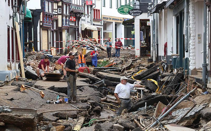 <p> People look over an area affected by flooding in Bad Münstereifel Germany, July 19, 2021. More than 195 people have been confirmed dead, while hundreds more remained missing after a record rainfall caused dams to burst and rivers to overflow into towns and streets across western Germany, Belgium, as well as parts of the Netherlands, Switzerland and northern France. </p>