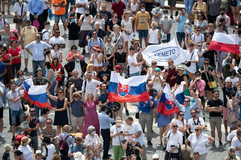 <p>Pilgrims holding the Slovak flag cheer in St. Peter&rsquo;s Square at the Vatican July 4, 2021, as Pope Francis announces he will visit their country Sept. 12-15. The visit will follow after the pope celebrates the closing Mass at an International Eucharistic Congress in Budapest, Hungary. (CNS photo by Vatican Media)  </p>