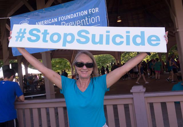 <p>Carleen Schmittendorf, of Rochester, poses with a sign before the start of the annual Out of the Darkness Community Walk Sept. 24 at Genesee Valley Park in Rochester. </p>