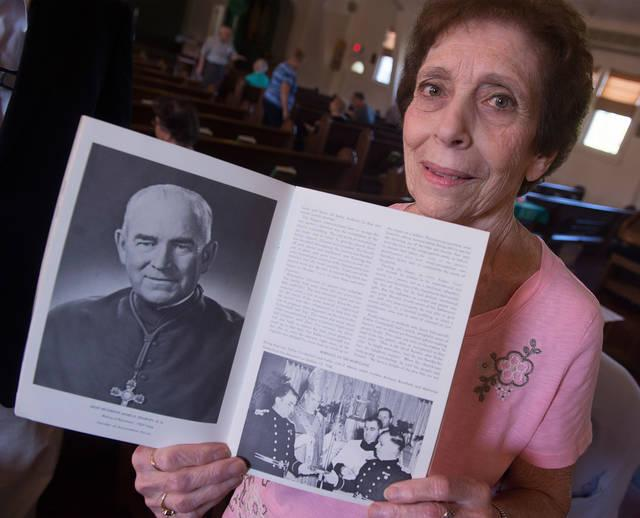 <p>Prior to the start of Mass Sept. 23, Rose Giovine, a lifelong parishioner of Rochester's Annunciation Church, holds a book from the church's golden anniversary.  </p>