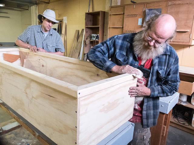 <p>St. Joseph's House of Hospitality volunteers John Rogowicki and Don Skillman sand a casket Oct. 24. (Courier photo by John Haeger)  </p>