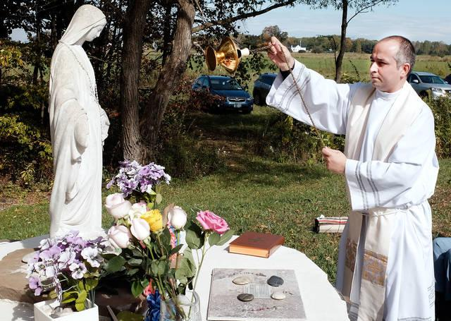 Father Daniel Ruiz-Sierra censes the statue of Mary at Linda Benson's farm in Groton Oct. 7 before parishioners of St. Anthony Church pray the rosary.